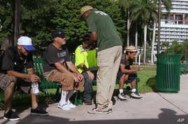 In this frame made from video Sept. 8, 2017, an official in Miami speaks with homeless people about moving to shelters ahead of powerful Hurricane Irma.
