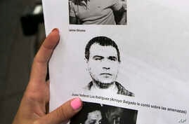 """A reporter holds a picture of Antonio """"Jaime"""" Stiusso, one of the country's most enigmatic spy chiefs, outside the prosecutor's office in Buenos Aires, Feb. 5, 2015."""