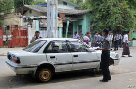 Burma police officers inspect a damaged vehicle at the scene of a small blast that happened close by the vehicle in Mandalay, July 22, 2013.