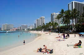 "People relax on the beach in Waikiki in Honolulu, March 13, 2017. As Hawaii begins to prepare for the possibility of a North Korean missile strike, the emergency management agency reiterates, ""Hawaii is still safe."""