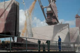 FILE - A worker watches corn being loaded into a grain ship in the port of Rosario, about 300 kilometers (190 miles) north of Buenos Aires, Argentina, April 5, 2006. Wednesday and explosion at the shipping hub killed one employee and injured eight ot