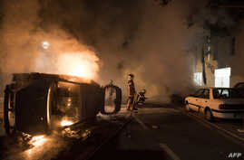 Firefighters work to put out a fire near a burning car in the Malakoff neighborhood of Nantes, France, July 4, 2018.