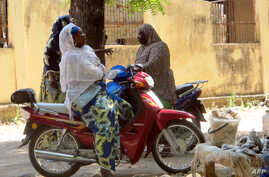 Women chatting while sitting on their bikes in a district of Maroua, northern Cameroon, Nov. 20, 2013.