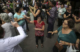 FILE - Elderly people dance on a street during the International Day of Older Persons in Sao Paulo's Avenida Paulista, Brazil, October 2013.