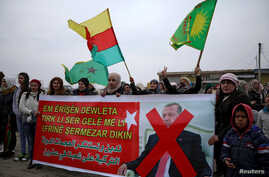 "People hold flags and carry a banner reading, ""We condemn and denounce the attacks of the Turkish government against our people in Afrin,"" during a protest against Turkish attacks on Afrin, in Hasaka, Syria, Jan. 18, 2018."