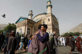 Afghans greet each other outside the Shah-e Doh Shamshira Mosque, on the first day of Eid al-Fitr, which marks the end of the holy month of Ramadan, in Kabul, Afghanistan, June 15, 2018.