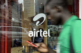 A man with his phone in hand walks past a window branded in an 'Airtel' logo on May 20, 2011 in the Kenyan capital, Nairobi.