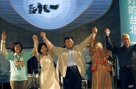 Taipei's new mayor-elect Ko Wen-je, center, raises his arms with family and friends to cheer with supporters at his campaign headquarters in Taipei, Taiwan, Saturday, Nov. 29, 2014.