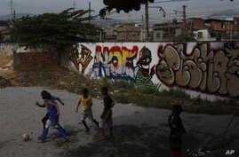 FILE - Children play soccer outside as they wait for the inauguration of a soccer pitch at the entrance of Jacarezinho shantytown in Rio de Janeiro, Brazil.