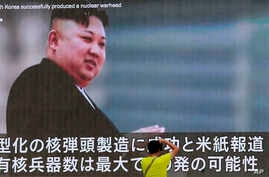 FILE - A man takes a photo of a TV news program showing an image of North Korean leader Kim Jong Un, in Tokyo, Japan, Aug. 6, 2017.