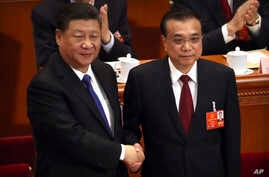 Chinese President Xi Jinping, left, shakes hands with Premier Li Keqiang after Li was re-elected as Premier during a plenary meeting of China's National People's Congress (NPC) at the Great Hall of the People in Beijing, March 18, 2018.