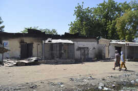 FILE - Women walk by homes destroyed by Boko Haram militants in Bama, Borno State, Nigeria.