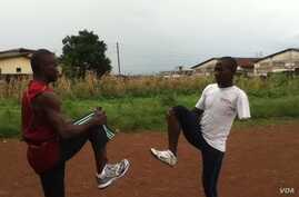 Mohamed Kamara and his coach, Abu Bakar Conteh, warm up before a training session ahead of the 2012 Paralympic. (VOA - N. deVries)