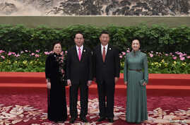 FILE - Vietnam's President Tran Dai Quang, second left, and his wife Nguyen Thi Hien, left, pose with Chinese President Xi Jinping and his wife Peng Liyuan during a welcome ceremony for leaders attending the Belt and Road Forum, at the Great Hall of