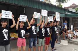 Protestors hold signs about the mass fish deaths in Nghe An Province, central Vietnam