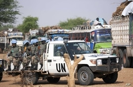 In this July 14, 2011 photo released by the African Union/UN Hybrid operation in Darfur (UNAMID), UNAMID Rwandan troops escort returnees during a repatriation operation for more than 200 displaced families returning from Aramba to their original vill