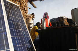 A youth displaced by the fighting charges batteries with solar panels at a makeshift shop in a camp for internally displaced persons at the United Nations base in Bentiu, Unity State, June 17, 2014.