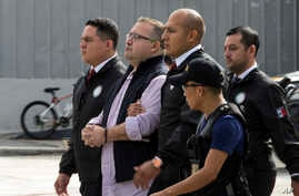 Mexico's ex-governor of Veracruz state, Javier Duarte, is escorted in handcuffs by police to an aircraft as he is extradited to Mexico City, at an Air Force base in Guatemala City, July 17, 2017.