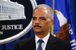 Attorney General Eric Holder listens during a news conference on charges filed against five Chinese military officials for cyber theft of business secrets, at the Justice Department in Washington, May 19, 2014.