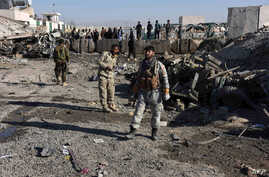 Afghan security personnel gather at the site of a suicide attack at a police compound in Maiwand district of Kandahar province on December 22, 2017.