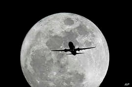 FILE - A commercial airliner crosses the first full Moon of the year, called the Wolf Moon over Whittier on its way to Los Angeles Airport, Jan. 4, 2015.