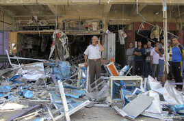 Residents stand among debris at one of the scenes of car bomb attacks that struck Baghdad July 19, 2014. A series of car bombs struck Baghdad on Saturday, killing 22 people, police and medics said. Car bombs exploded in three mainly Shi'ite districts