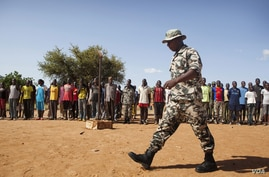 A Malian solider walks in front of people during a training camp of the FLN  movement (North Liberation Forces) in Sevare September 24, 2012. The FLN is a part of a militia which trains youths from all over the country and operates in government-cont