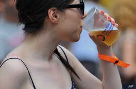 FILE - A woman is seen consuming a beer.