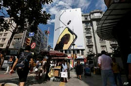People walk past an advertising billboard for a smartphone in an upscale neighborhood in Istanbul, Turkey, Aug. 15, 2018.