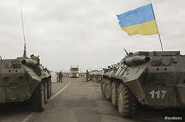 Ukrainian soldiers and armoured personnel carriers guard a checkpoint near the village of Salkovo, in Kherson region, adjacent to Crimea, March 20, 2014.