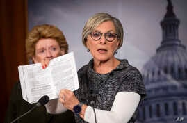 Senator Barbara Boxer (R) holds up a passage from the Affordable Care Act concerning health care benefits for women during a news conference on Capitol Hill in Washington, Sept. 30, 2013.