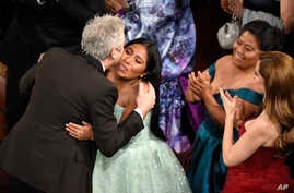 "Yalitza Aparicio, right, congratulates Alfonso Cuaron in the audience as he is announced the winner of the award for best cinematography for ""Roma"" at the Oscars on Sunday, Feb. 24, 2019, at the Dolby Theatre in Los Angeles."
