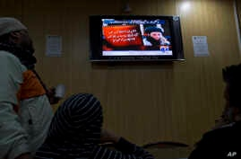FILE - People watch a news report on TV about the leader of Pakistani Taliban leader Fazlullah Khurasani, at a coffee shop in Islamabad, Pakistan, Nov. 7, 2013.