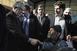 Greece's Prime Minister Lucas Papademos, left, greets a homeless man during a New Year's meal for the homeless people distributed by the municipality of Athens, January 1, 2012.