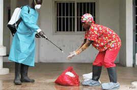 A Liberian Red Cross employee disinfects after removing a body suspected of having Ebola, Monrovia, September 2014. (Credit: International Alert)