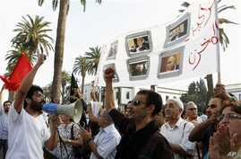 Anti-government protesters from 'the 20th February', the Moroccan Arab Spring movement, shout in front of parliament as they hold a banner with portraits of political parties leaders treated like puppets of the 'Makhzen', a Moroccan Arabic term for t