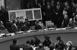 In this October 25, 1962 file photo, U.S. Ambassador Adlai Stevenson, far right, describes aerial photographs of launching sites for intermediate range missiles in Cuba during an emergency session of the United Nations Security Council at U.N. Headqu
