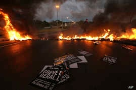"Military policemen clear a flaming barricade on an access highway to Brasilia, Brazil, June 30, 2017. Signs that read in Portuguese ""General strike"" are strewn on the road."