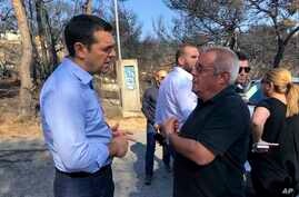 Greece's Prime Minister Alexis Tsipras (L) visits the burnt area of Mati, east of Athens, July 30, 2018.