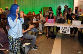 While activists and lawyers at the table at right offer help and information, Hanadi Al-Haj prays in the Tom Bradley International Terminal at Los Angeles International Airport as she waits for her Yemeni mother to arrive, June 29, 2017, in Los Angel