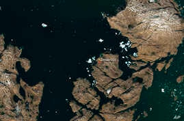 The satellite image, which was captured by Sentinel-2A on July 9, 2018, provided by European Space Agency esa on July 18, 2018 shows a huge iceberg perilously close to the village of Innaarsuit on the west coast of Greenland.