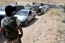 Hezbollah members escort a convoy of Syrian refugees at the border town of Arsal, Lebanon, July 12, 2017. Hezbollah and the Syrian army Friday launched an offensive against insurgents along the border.