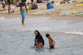 A Muslim woman wears a burkini, a swimsuit that leaves only the face, hands and feet exposed, on a beach in Marseille, France, August 17, 2016.