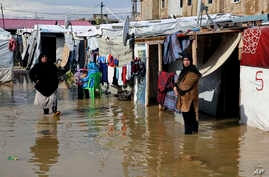 Syrian refugees stand in a pool of mud and rain water at a refugee camp, in the town of Bar Elias, in the Bekaa Valley, Lebanon, Thursday, Jan. 10, 2019.