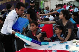 Syrian refugee children scuffle with a waiter as they try to get a pack of food at an iftar (breaking fast) event open to public during the Muslim holy fasting month of Ramadan in central Istanbul, July 17, 2014.
