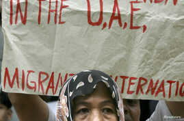 FILE - A Filipino Muslim woman joins the picket led by a migrant workers group for human rights at the embassy of the United Arab Emirates (UAE) in Manila.