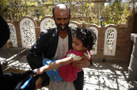 A Yemeni health worker marks a finger of a girl after giving her a polio vaccination during a house-to-house polio immunization campaign in Sanaa, Yemen, Tuesday, Nov. 10, 2015.