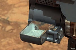 This image from NASA's Curiosity rover shows the first sample of powdered rock extracted by the rover's drill. (NASA/JPL-Caltech/MSSS)