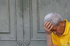 A pensioner waits in front of the main entrance of a National Bank branch to receive part of his pension in central Athens, Greece July 9, 2015.