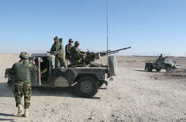 Afghan National Army soldiers guard at a checkpoint on the way to the Sangin district of Helmand province, Afghanistan, Wednesday, Dec. 23, 2015.